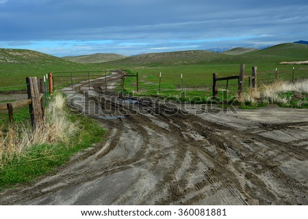 The entrance to a Central California ranch requires negotiating a muddy road in winter.  - stock photo