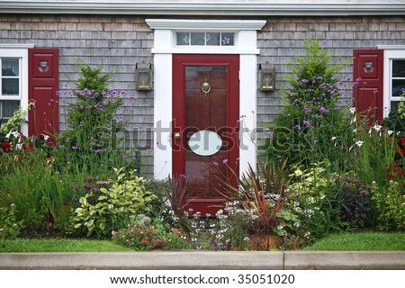 The entrance to a home surrounded by yew shrubs and annual and perennial flowers. - stock photo