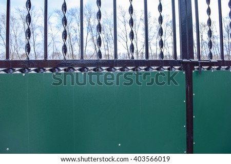 The entrance to the courtyard of the house. A metal gate, with forged elements and painting of metal parts. - stock photo