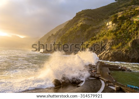 The entrance to the port in the waves of a raging storm at sunset. Cinque Terre, Italy - stock photo