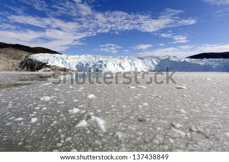 The Eqi glacier in Greenland. This glacier is 70 km north of Ilulissat in Disco Bay and is one of the most active glaciers in Greenland. It constantly calving and breaking ice pieces into the fjord. - stock photo