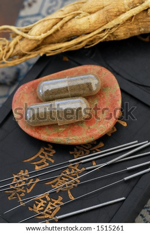 The essence of Chinese medicine: herbal capsule, Ginseng root, and acupuncture needles. - stock photo