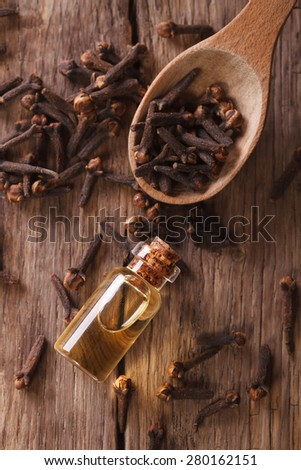 The essence of cloves in the bottle close-up on the table. vertical view from above  - stock photo