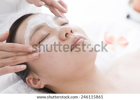 The esthetician applying beauty mask a female face