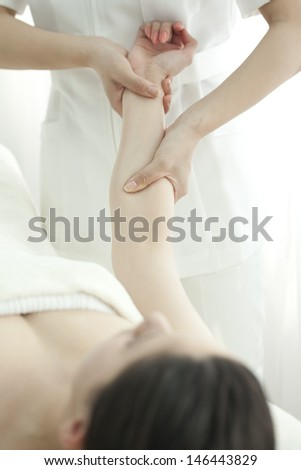 The esthetician who massages an arm - stock photo