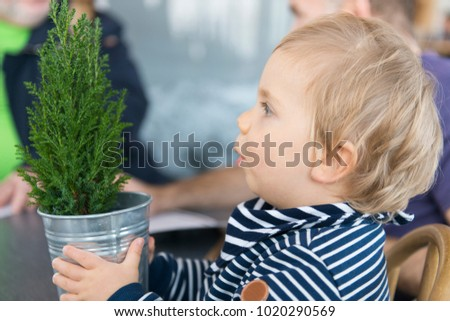 The European kid holds a small fir in his hands and looks at her with surprise