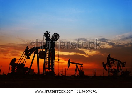 The evening of the oilfield, pumping unit and the silhouette of oilfield derrick