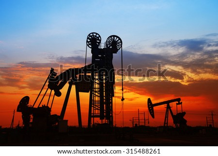 The evening of the oilfield, pumping unit and the silhouette of oilfield derrick - stock photo