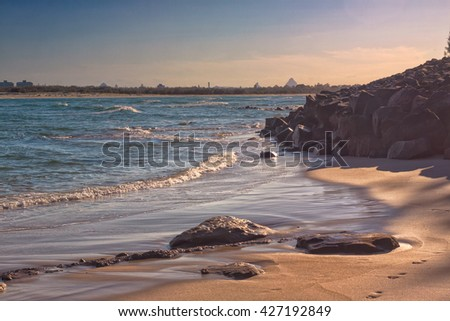 The evening sun casts long shadows on the sand of a beach in Caloundra, Queensland, Australia.  You can see the Glasshouse mountains in the background. - stock photo