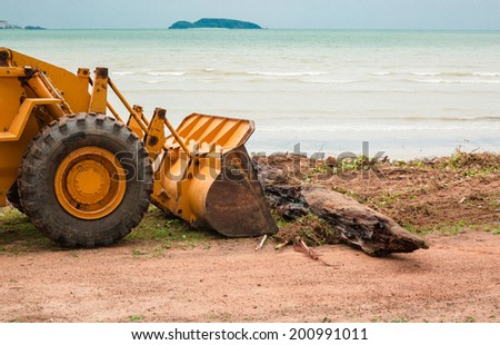 The excavator and wastes at sea beach - stock photo
