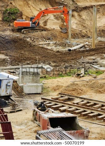 The excavator digs the earth under the building base, on forward  rails for the tower crane - stock photo