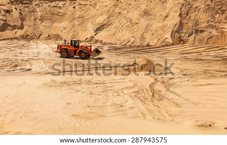 The excavator works in the sandy quarry, sand mining, sand pit - stock photo