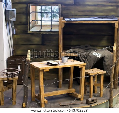 The exhibit of the Museum -  the prisoner's cell: table, chair, bench, padded jacket, grill, sink, barbed wire