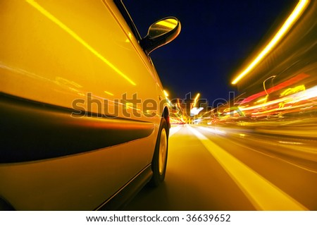The exterior of a car driving through an urban envrionment, with streaks of light passing by - stock photo