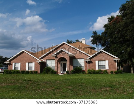 The exterior of a one story brick residential home. - stock photo