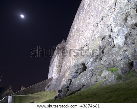 The exterior wall of Edinburgh Castle is built on a solid rock foundation. Heavy stone Fortifications protect for the inner fortress. This night exposure shows the moon with a bit of movement. - stock photo