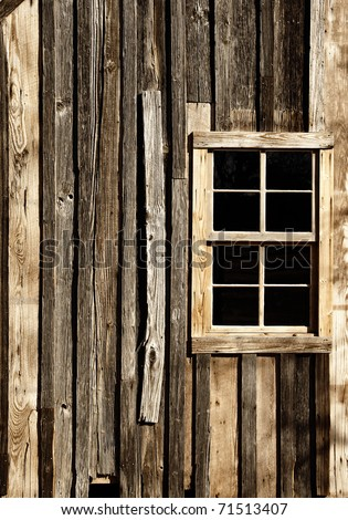 The external window and wall of a vintage wood house in the American West (sepia tint). - stock photo