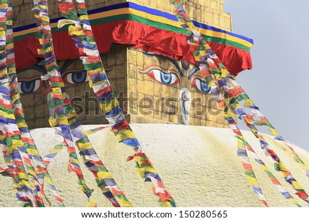 The eyes of the Buddha look to the 4 cardinal points from the top of the big stupa of Boudhanath-Bodhnath with buddhist prayer flags hanging from its 13 storey pyramidal golden tower. Kathmandu-Nepal.