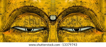 The eyes on a golden carving of Buddha's face. - stock photo