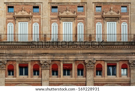 """The facade of a historic palace at the place """"Piazzo Maggiore"""" of Bologna in Italy - stock photo"""