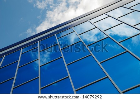 The facade of a modern building from blue glass reflects the sky - stock photo
