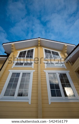 The facade of the wooden house with large Windows on the background of blue sky