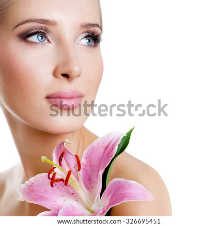 The face of a beautiful girl with a fresh flower lily - stock photo