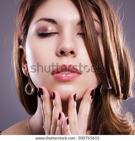 The face of a beautiful woman with bright makeup closeup. - stock photo