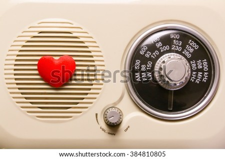 The face of a vintage radio with a red love heart - stock photo