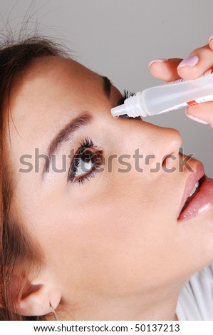 The face of a young pretty woman putting eye drops in her dry eyes to. get relief for her irritated eyes. - stock photo