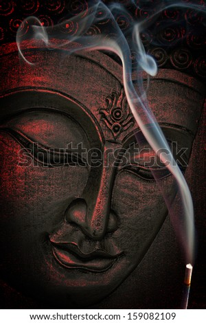 the face of Buddha with incense - stock photo