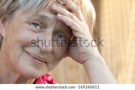The face of the elderly woman is photographed by a close up.