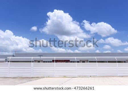 The factory building with concrete fence foreground and the blue sky