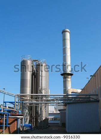The factory chimney photographed on a background of the blue sky