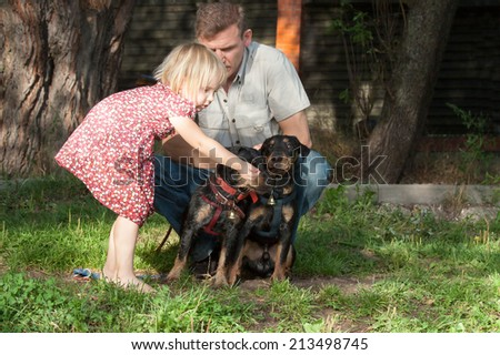 The fair-haired girl stretches something to two dogs terriers with hand bells under supervision of the father - stock photo