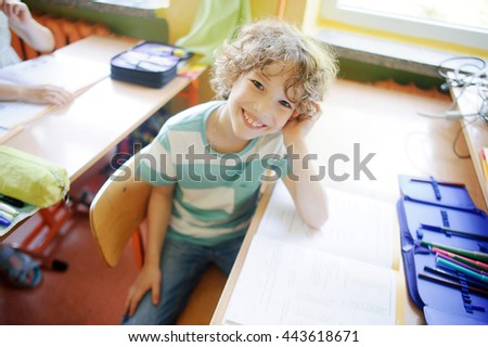 The fair-haired school student sits at desk in a class. On a school desk the open textbook and a pencil box. The laddie has an excellent mood. He looks in the camera and smiles. - stock photo