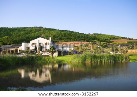 The Fairview wine farm in South Africa, overlooking a large reservoir dam. The Paarl, Afrikaans Language monument is just visible in on the horizon - stock photo