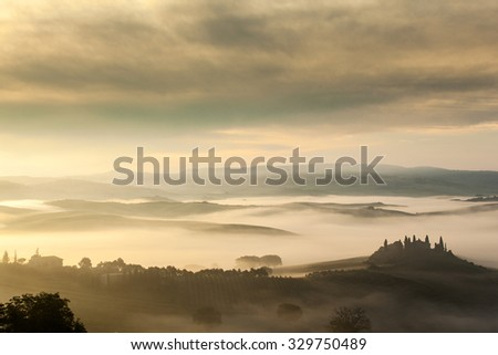 The fairytale foggy landscape of Tuscan fields at sunrise