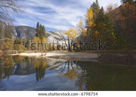 The fall colors and gray granite cliffs of Yosemite reflected in smooth water of Merced river.