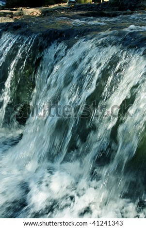 The falls flow in mountains - stock photo