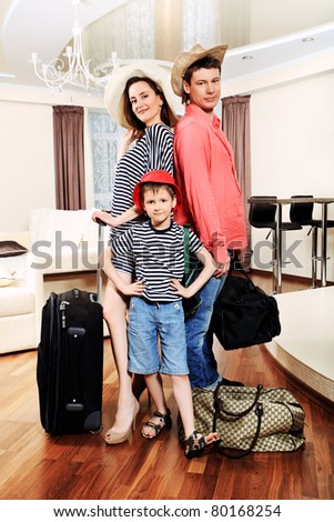 The family at home with a big suitcases is going to vacation. - stock photo