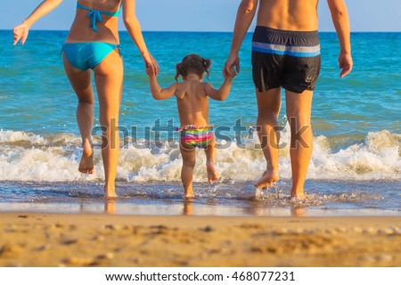 The family - father, mother and baby are going to swim in sea at sunset