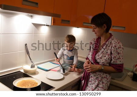 The family is cooking pancakes at kitchen - stock photo