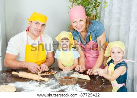 The family is preparing dough, Mom keeps the pan with the rolls - stock photo