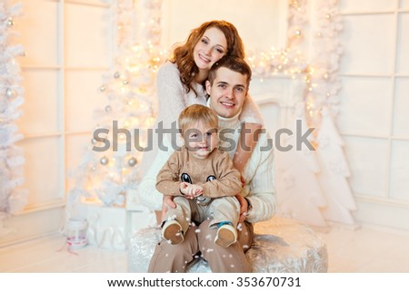 The family - mother, father and son in bright clothing embrace on a background of bright Christmas decorations - stock photo