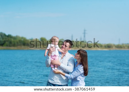 the family of three people has a rest outdoors. Mother, the father and their little daughter pose for a photo-shoot.