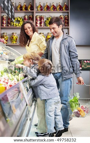 The family with children chooses products in shop - stock photo