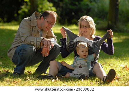 The family with the son sits on a grass in park. - stock photo