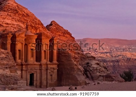 The famous Ad Deir, often also refered to as Monastery, in the ancient nabbatean city of Petra in Jordan at sunset with a view to the city of Wadi Musa. - stock photo
