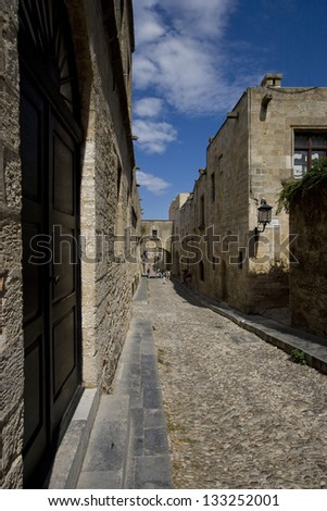 The famous cobblestone Street of the Knights, one of the best-preserved medieval streets in existence, at the old (medieval) town of Rhodes, Greece - stock photo